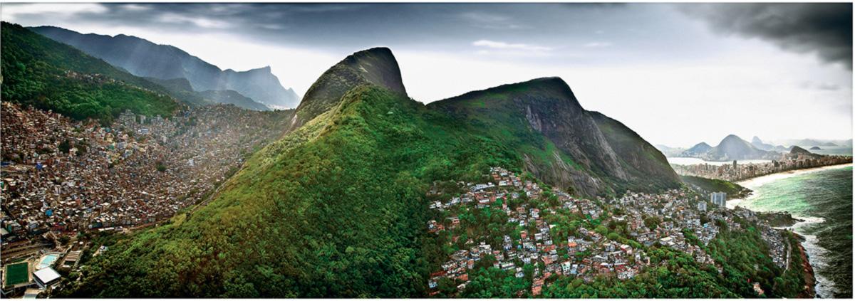 A favela da Rocinha, à esquerda, encontra com a do Vidigal, na Zona Sul. Ao fundo, as antigas referências, diminuídas: o Corcovado, a Lagoa, Ipanema e o Pão de Açúcar