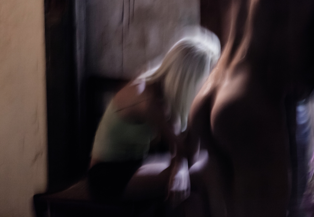 No final da tarde, as travestis se reúnem no hall em frente aos banheiros, onde fumam e conversam enquanto aguardam a fila para tomar banho; várias delas circulam nuas