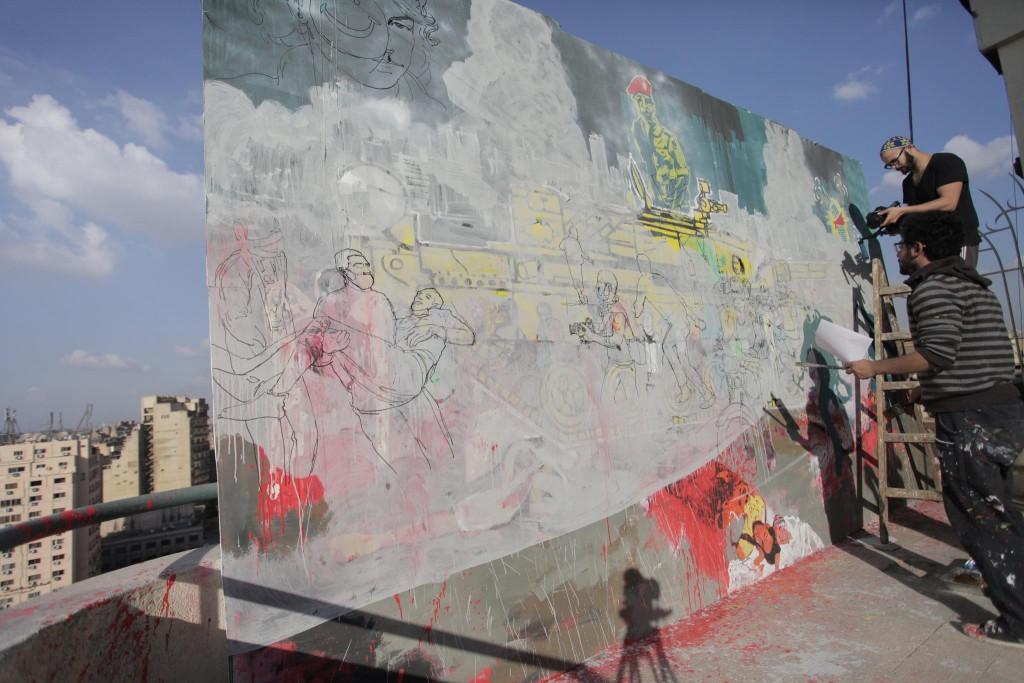Hamdy e seu amigo Ammar pintam um painel inspirado nas manifestações