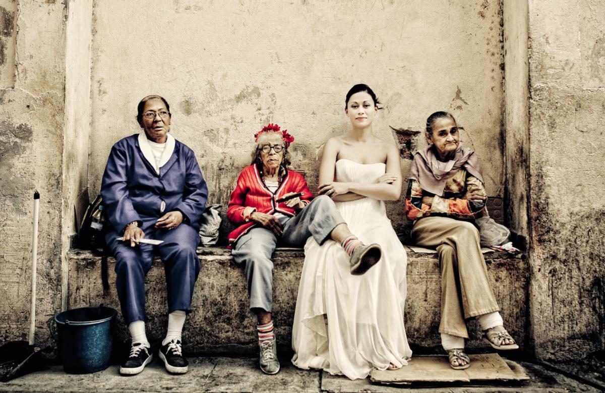 """Por dinheiro, cubanas posam com uma noiva em Havana. Herói da ficção de Leonardo Padura, Mario Conde vive numa cidade que é o inverso de um paraíso de trabalhadores, e se considera """"o merdinha de um detetive particular num país onde não existem detetives nem pessoas particulares"""""""