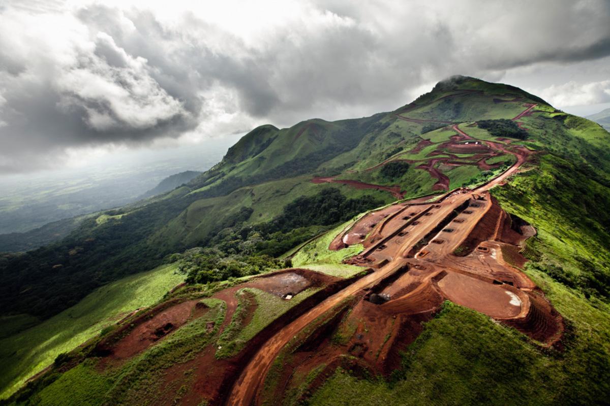 O solo vermelho das montanhas Simandou, na paupérrima Guiné, revela uma das maiores reservas de ferro do mundo; objeto de uma investigação de suborno e de uma disputa internacional que envolve grandes mineradores como a Rio Tinto e a Vale, a jazida permanece inexplorada