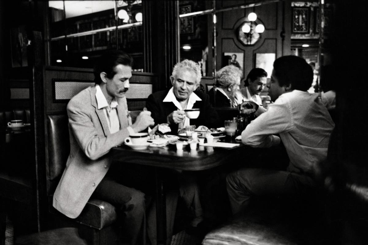"""Jack Henry Abbott, de bigode, toma chá em Nova York com Norman Mailer e o editor Erroll McDonald. Mailer ficou impressionado quando começou a trocar cartas com Abbott; achou que ele escrevia """"de forma intensa, sem firulas"""", com uma """"voz única"""""""