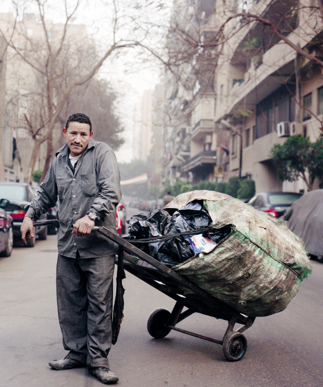 Sayyid Ahmed trabalha no sistema informal de coleta do Cairo, pago pelos moradores; veste-se com sapato e roupa largos e usados, achados no lixo, mas em sua casa tudo é novo em folha