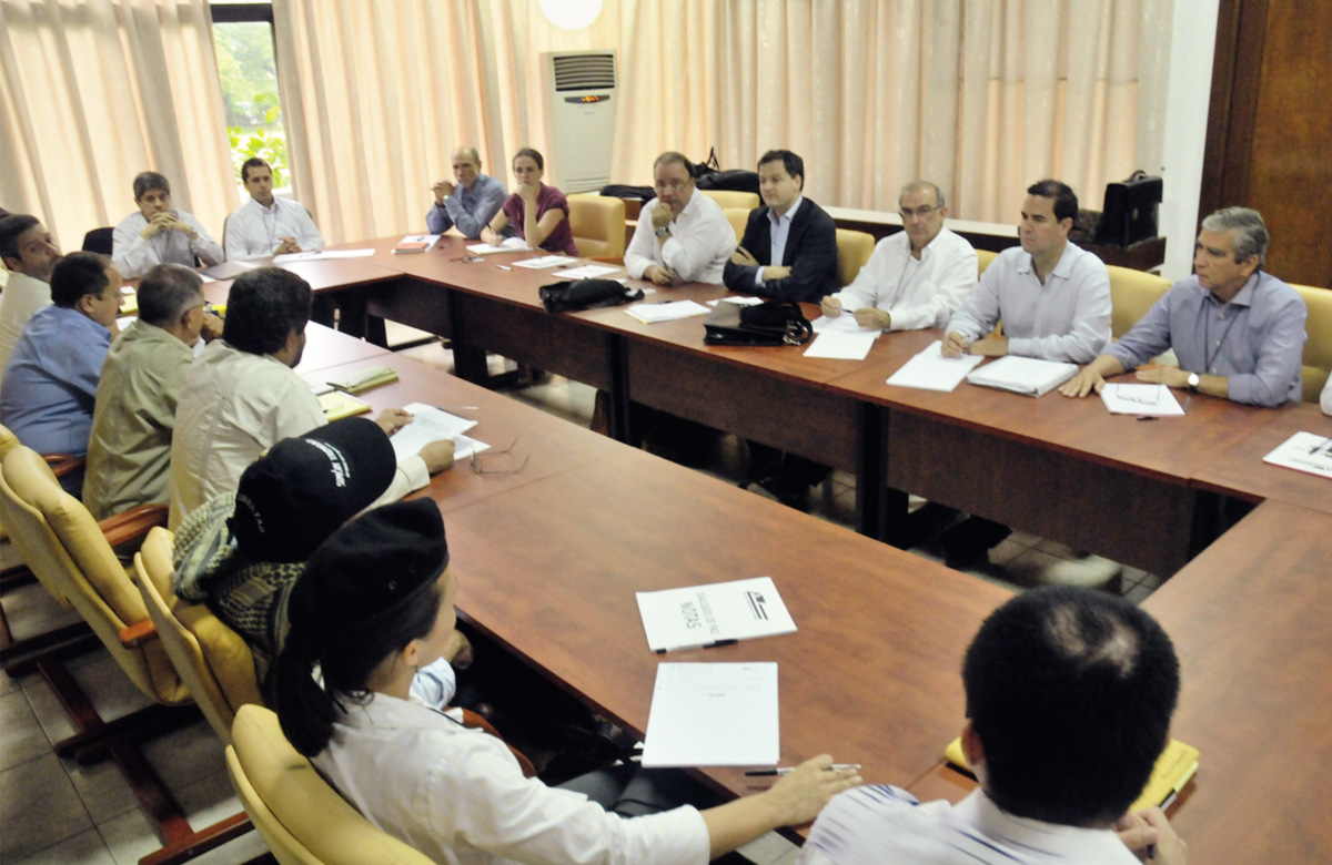 Em Havana, sentam-se à mesa emissários das Farc (em primeiro plano) e do governo colombiano. Iniciado há vinte meses, o diálogo abarca cinco pontos, incluindo o narcotráfico e a futura participação de guerrilheiros na política. A demora para um acordo final fortalece os opositores da negociação