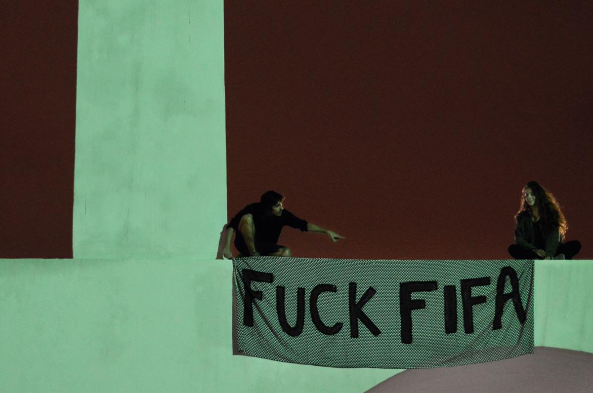 """Ciro e uma amiga penduram uma faixa contra a Fifa nos Arcos da Lapa. """"Sempre amei futebol, mas não sabia como reagiria diante dos jogos. Minha presença no ato já me dava uma pista"""", diz ele"""