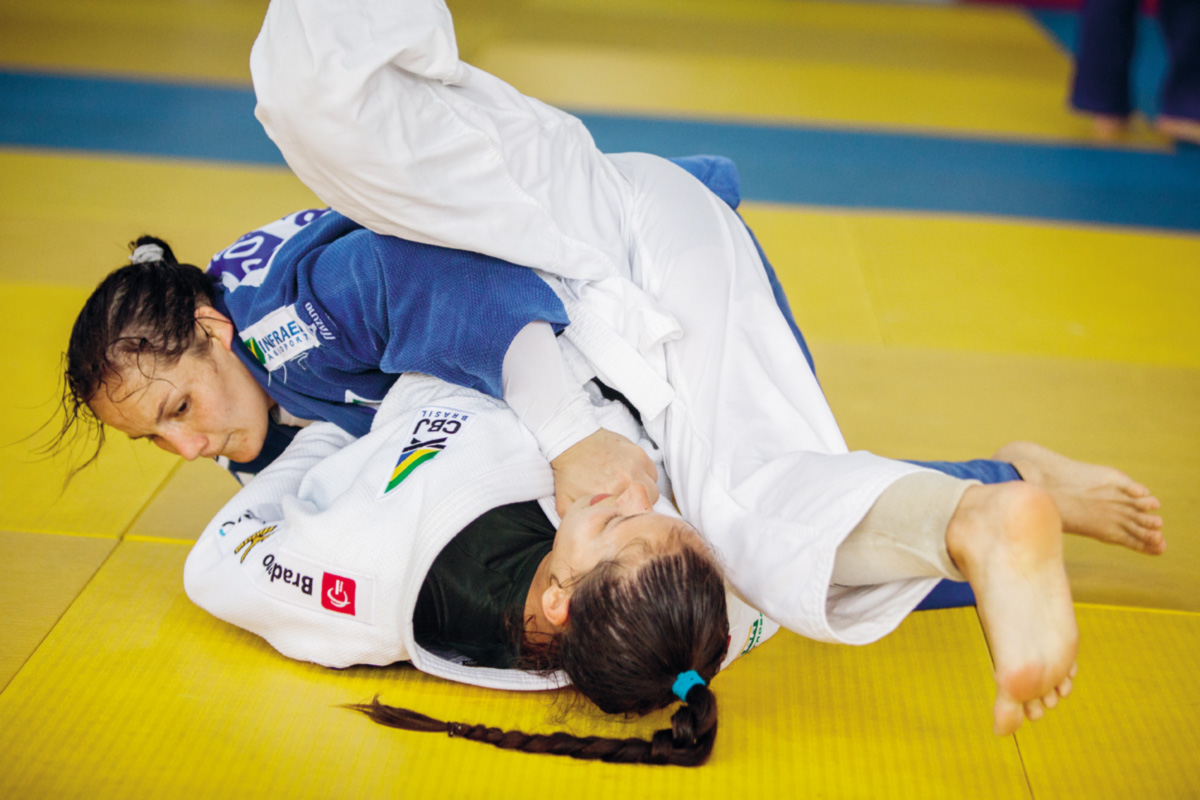 A gaúcha Maria Portela, de azul, enfrenta a <i>sparring</i> Alexia Castilhos durante os preparativos para a Olimpíada. Como é bem menor do que atletas de sua categoria, Maria procura compensar a defasagem com um estilo de luta mais ofensivo