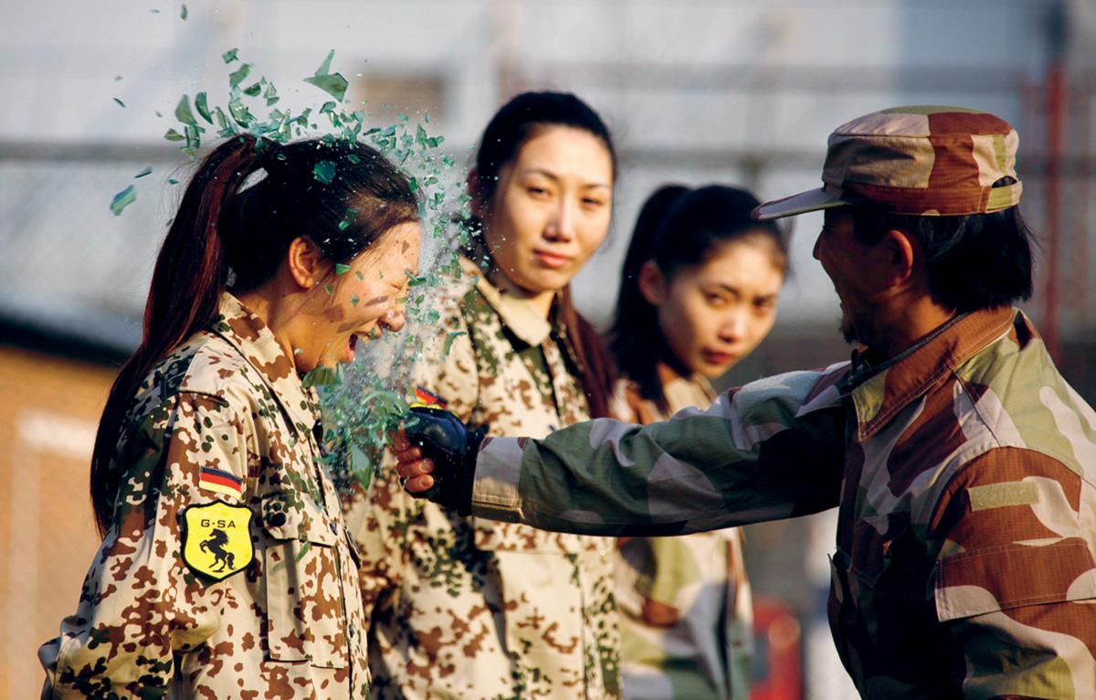 Ter uma garrafa estilhaçada contra a cabeça, e não se intimidar, faz parte do duro treinamento para guarda-costas feminino na China