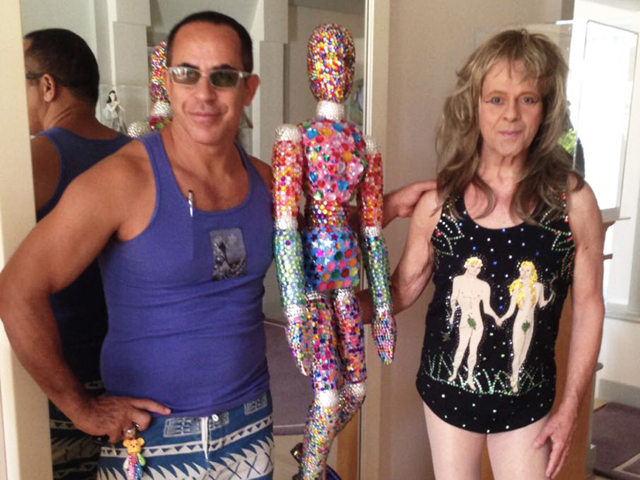 Mauro Oliveira com a obra que ele deu de presente a Simmons (montado como drag queen, à direita), no seu aniversário de 65 anos. A estátua é composta de três mil cristais, representando as pessoas que ele ajudou em sua carreira
