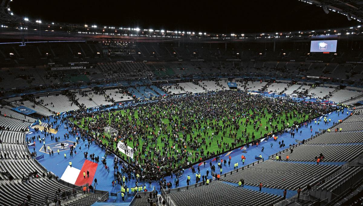 Torcedores ocupam o gramado depois da explosão de bombas nas cercanias do Stade de France, em 2015. Para uma parte dos intelectuais franceses, campanhas de combate a símbolos religiosos, como o véu e o burquíni, e a segregação de jovens pobres nas periferias impulsionam o terrorismo