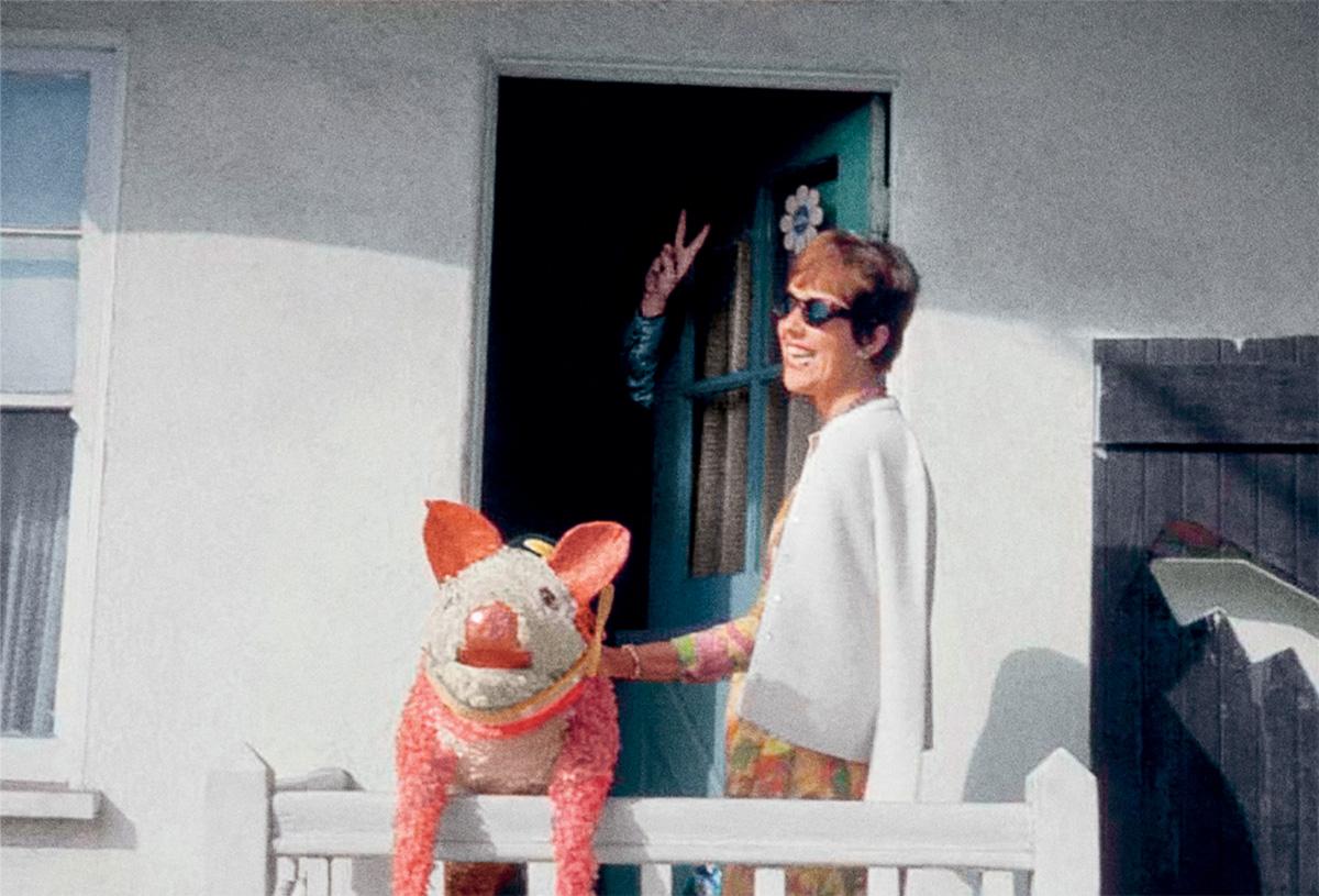 """Thomas Pynchon em 1965, fazendo o sinal de """"paz e amor"""", enquanto sua amiga Phyllis Gebauer segura a piñata que lhe deu de presente. O romancista adora porcos e já desenhou o rosto do animal ao lado de seu nome num autógrafo"""