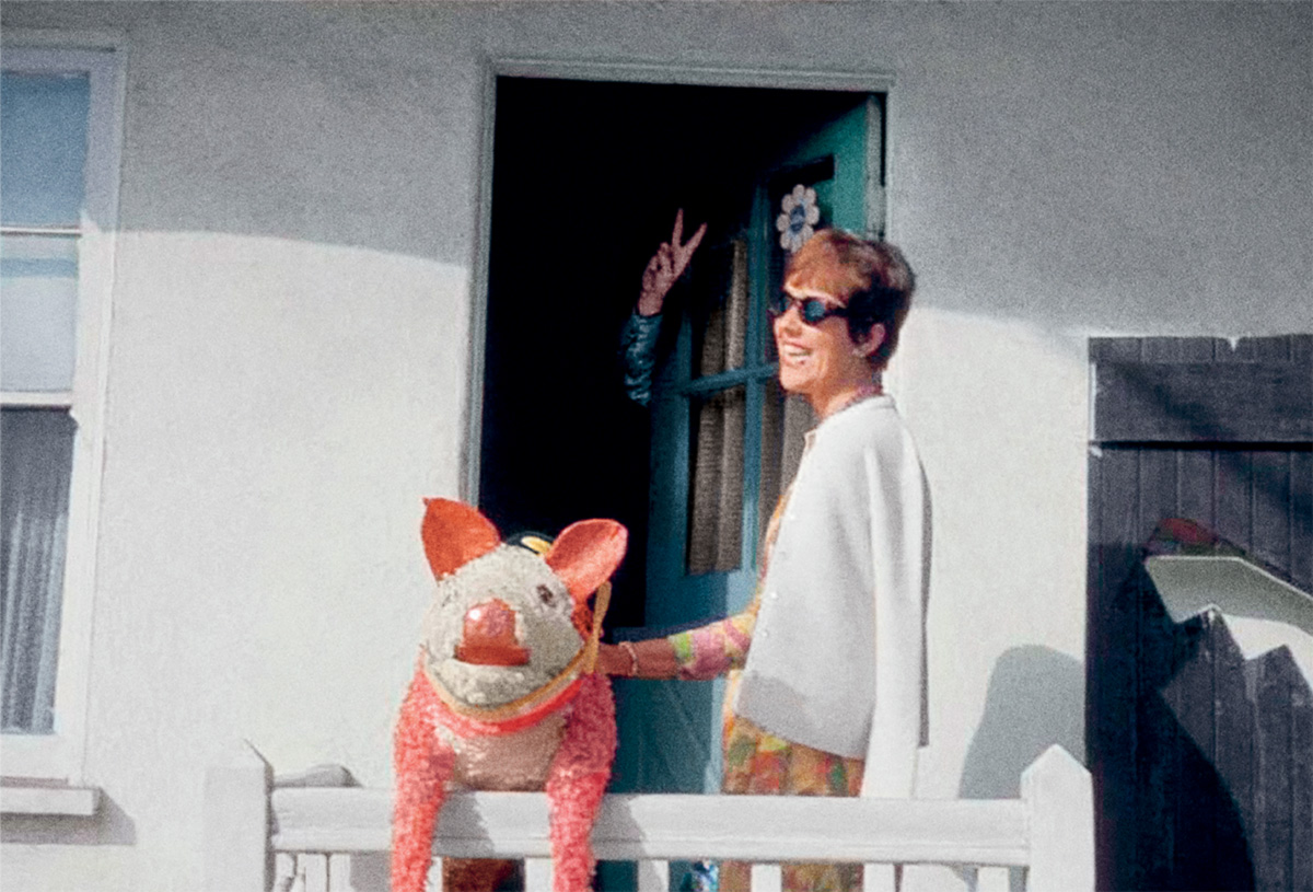 Thomas Pynchon in 1965, making the peace sign in the background, while his friend Phyllis Gebauer holds the pig piñata she gave him as a present. The novelist loves pigs and has drawn pig faces next to his name on autographs.