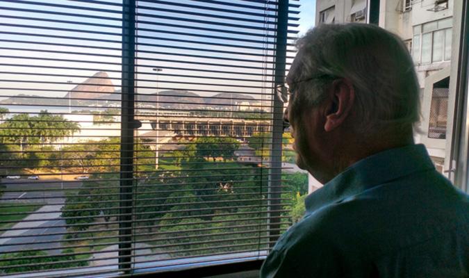 """Garcia-Roza em seu escritório com vista para a Baía de Guanabara: """"Não fico querendo ler tudo porque senão vou ficar sabendo como se faz literatura brasileira e eu não escrevo literatura brasileira. Eu escrevo a minha literatura."""""""