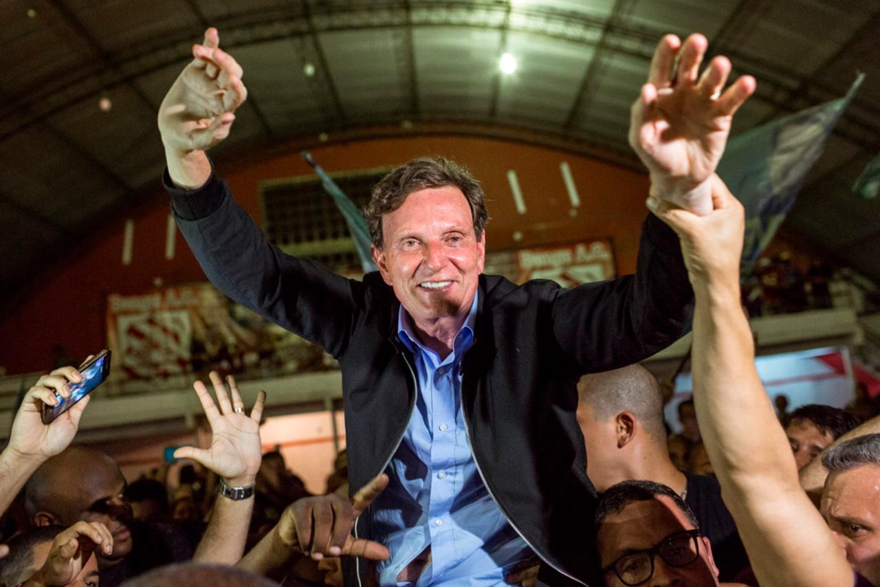 """Crivella comemorando a eleição. Os sonhos de campanha que uniam o carnaval e os evangélicos ruíram na Sexta-Feira Gorda: sem avisar, Crivella não foi ao Sambódromo para abrir oficialmente a festa. Nem deu as caras nos dias dos desfiles. Chiquinho de Carvalho, deputado e presidente da Mangueira, se rebelou: """"Ele não sabe do que somos capazes."""""""