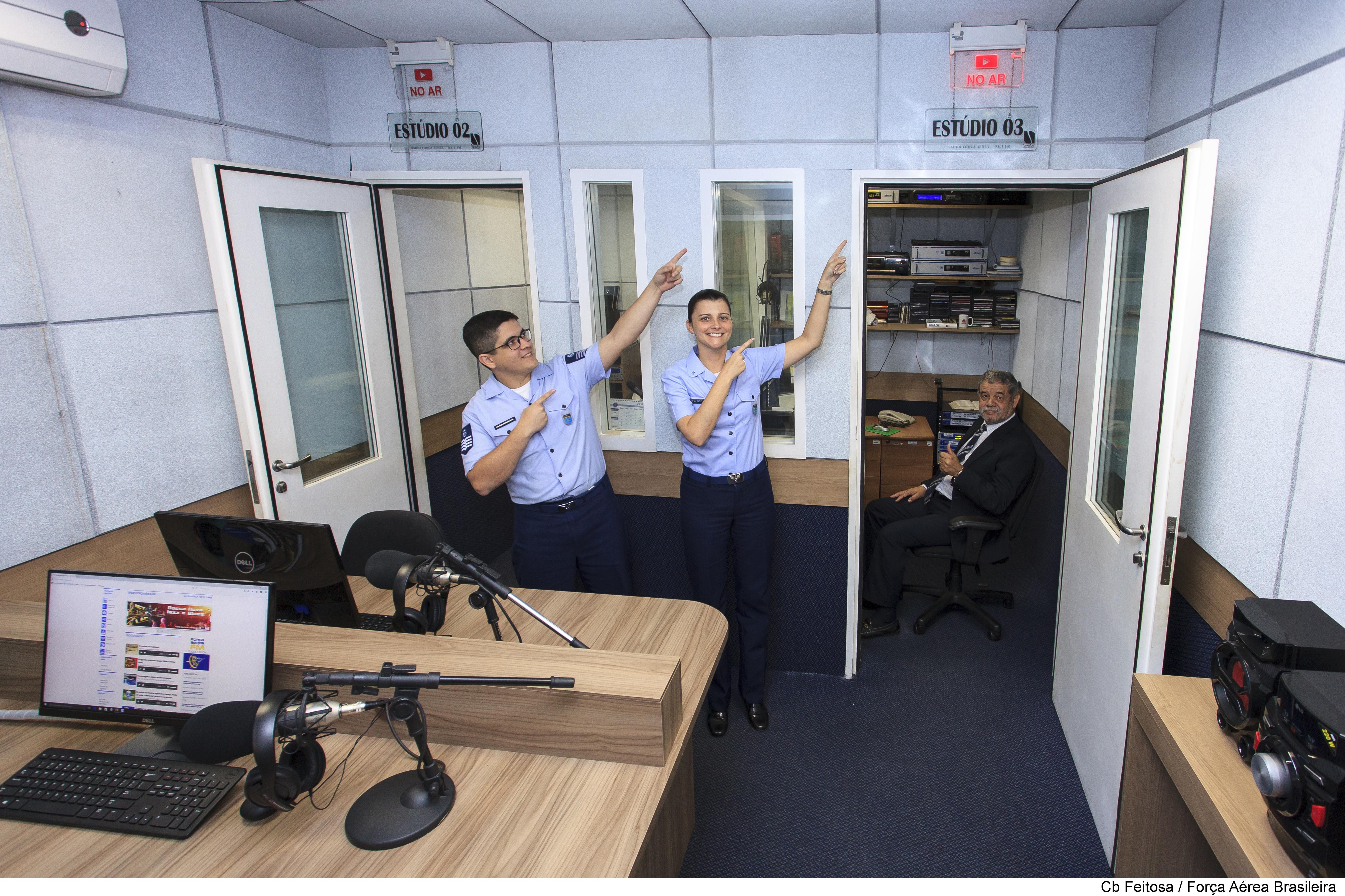 A jornalista Raquel de Souza Alves, cercada pelos colegas da Força Aérea FM, batiza os programas: Ponte Aérea, 14 Bis, Jet Lag, Voo Noturno, Top FAB.