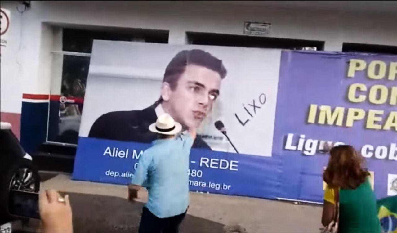 Cartaz do deputado federal Aliel Machado é alvejado com ovos após ele votar contra o impeachment de Dilma Rousseff. Na data da votação, ele transferiu a família para Brasília após receber ameaças