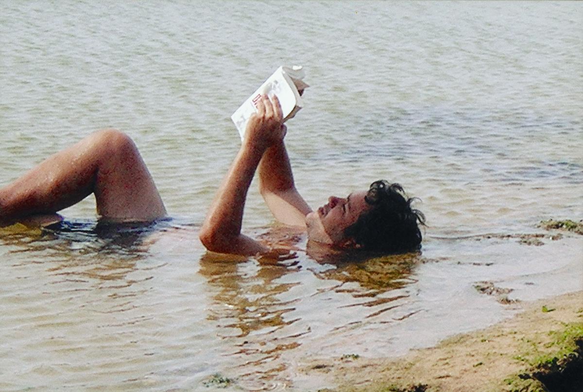 Alexandre Abreu Gontijo em pose natural: livro, mar e sol. Para chegar ao Paraíso, faltaria apenas acrescentar uma banca de jornal, um amigo, uma carona e uma bola de futebol