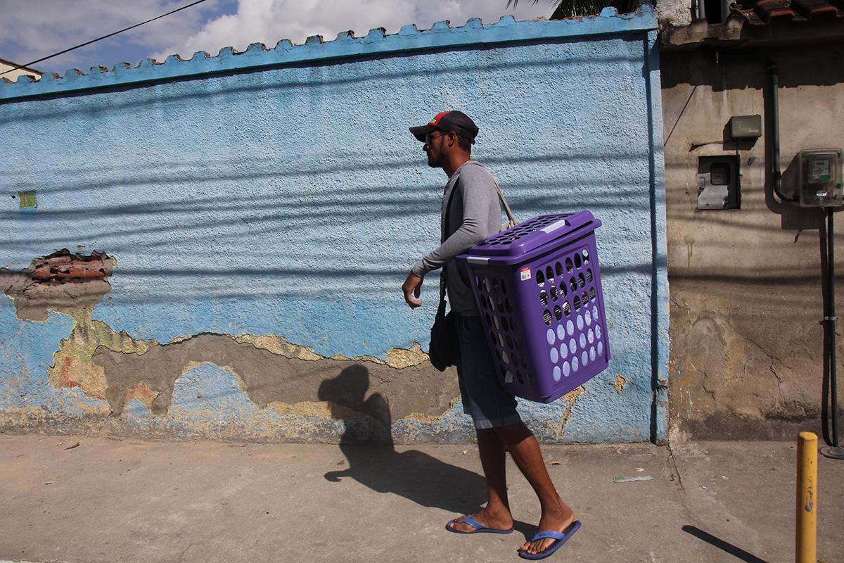 Antonio Marciano carrega sua cesta de mercadorias pelas ruas de Duque de Caxias, Rio de Janeiro