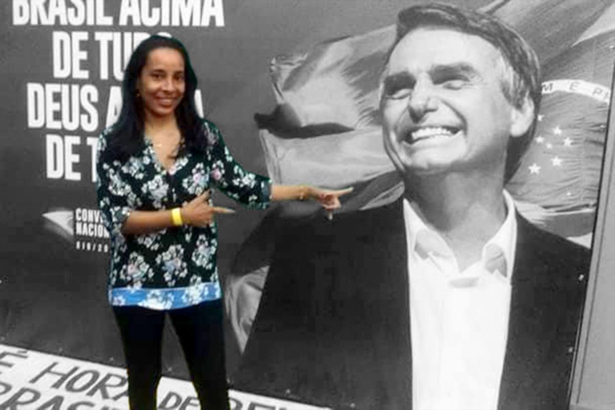 Lucia Helena Ribeiro posa em frente a cartaz do presidenciável do PSL, na convenção que oficializou a candidatura