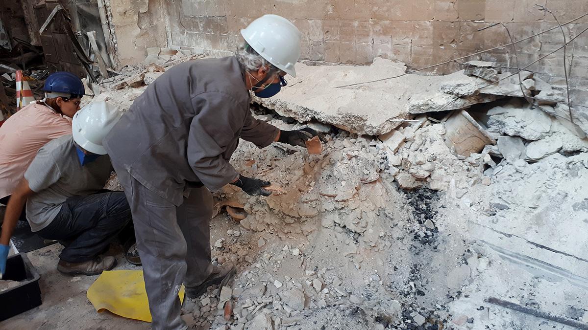 A arqueóloga Angela Rabello resgata fragmentos de cerâmica indígena em meio aos escombros do incêndio do Museu Nacional. À direita vê-se um vaso marajoara recuperado praticamente intacto no fim de janeiro.