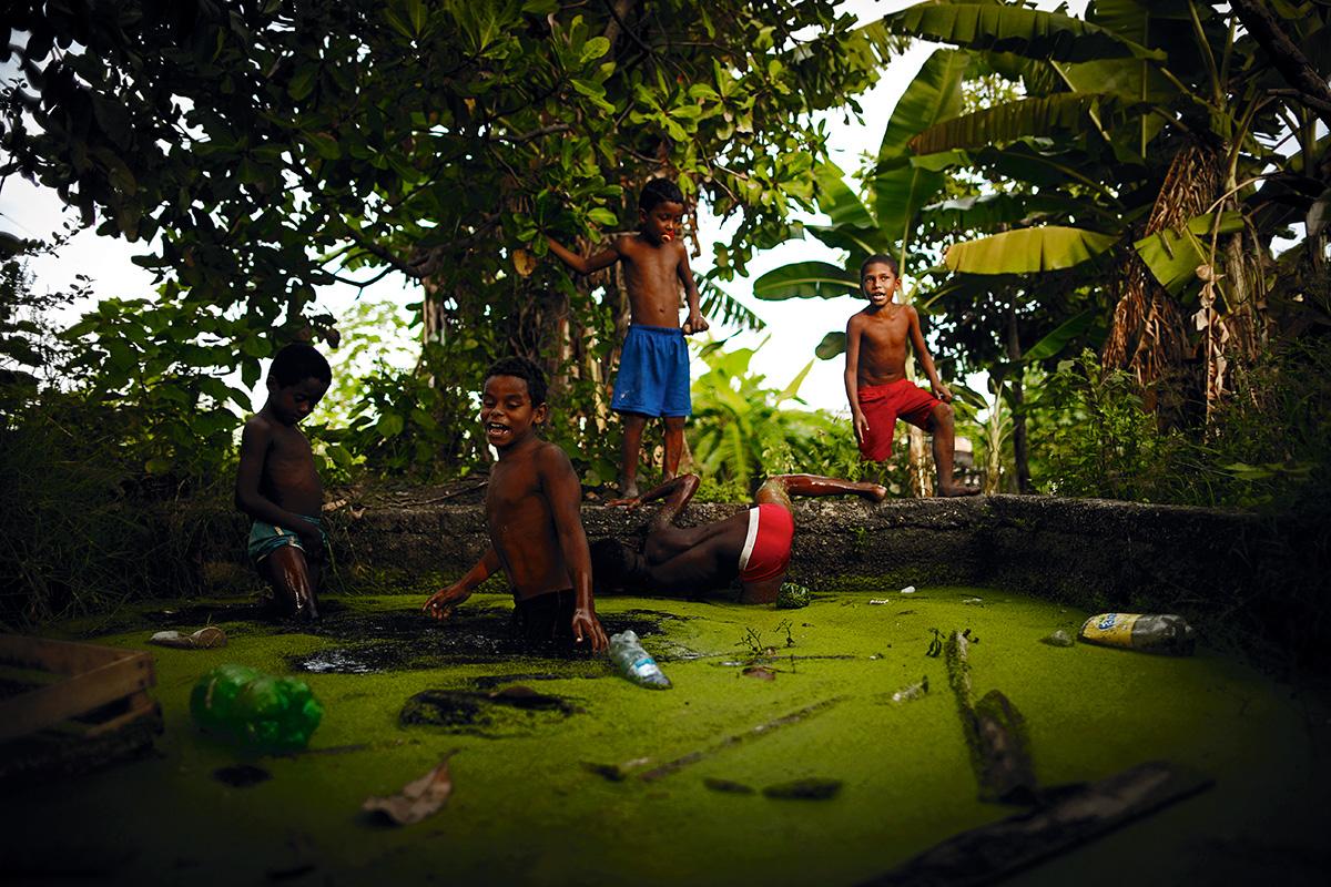 Na Zona Norte carioca, a favela Parque Everest abriga três tanques que acumulam lixo e água da chuva. Crianças não só os convertem em piscinas como vendem as rãs que aparecem por lá