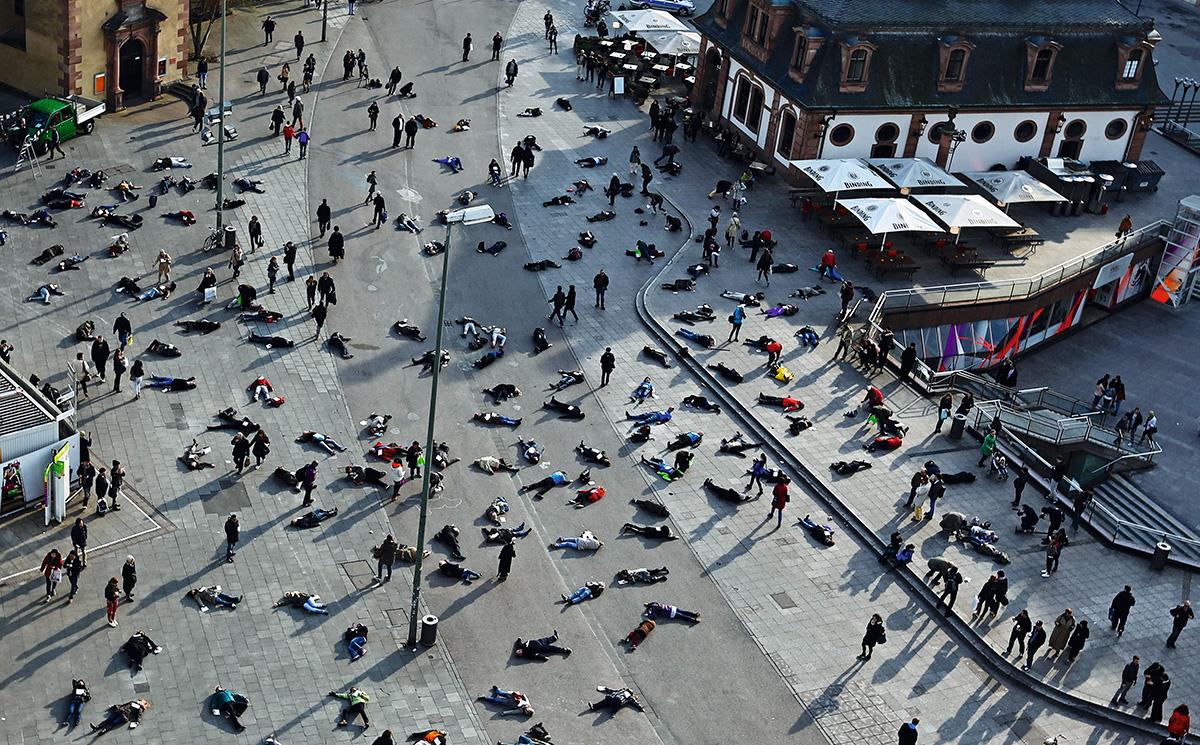 Para os disseminadores de <i>fake news</i>, a imagem mostra pessoas morrendo nas ruas, vítimas de Covid-19. Na realidade, era uma performance, realizada em Frankfurt, em março de 2014, em homenagem às 528 vítimas do campo de concentração nazista de Katzbach na Segunda Guerra Mundial