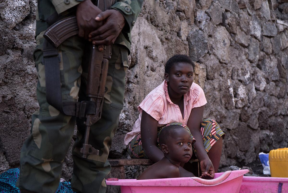 Em zona de conflito e sem acesso à água encanada, familiar de vítima do ebola dá banho no irmão
