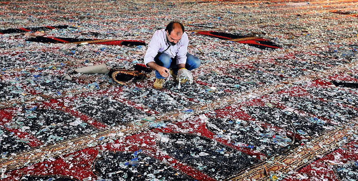 """Um homem recolhe cacos de vidro sobre o tapete de uma mesquita, no dia seguinte à explosão: """"É como se uma fada tivesse ladrilhado Beirute inteira com pó de vidro"""", descreve Halawi"""