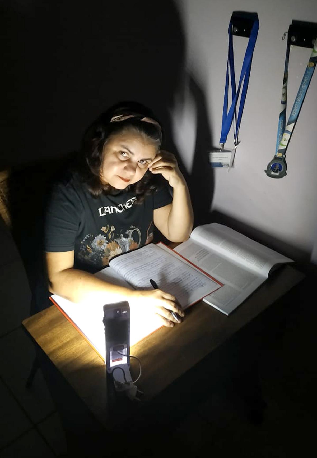 Dulcivânia Freitas estuda à luz de luminária de emergência –