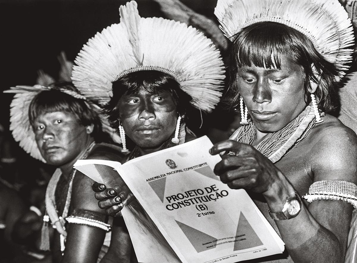 Os indígenas Mro-o, Tomtu e Nzoikamrekti Kayapó leem em 1987 o projeto da nova Constituição, promulgada no ano seguinte: o artigo 231 define que o direito dos povos indígenas às suas terras é originário, ou seja, anterior à própria Constituição –