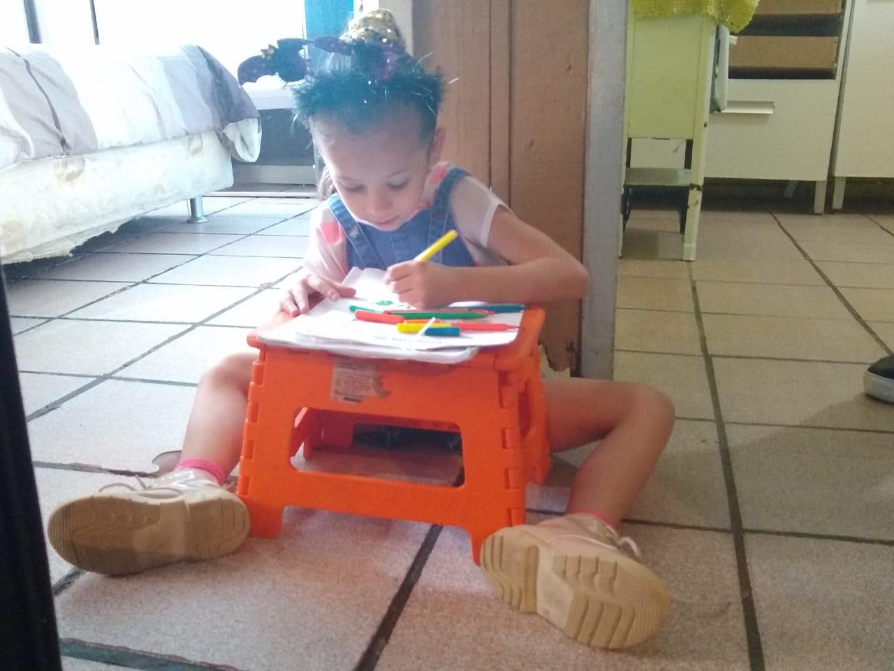 Giovana, que ainda não vai à escola, colorindo desenhos em sua mesinha