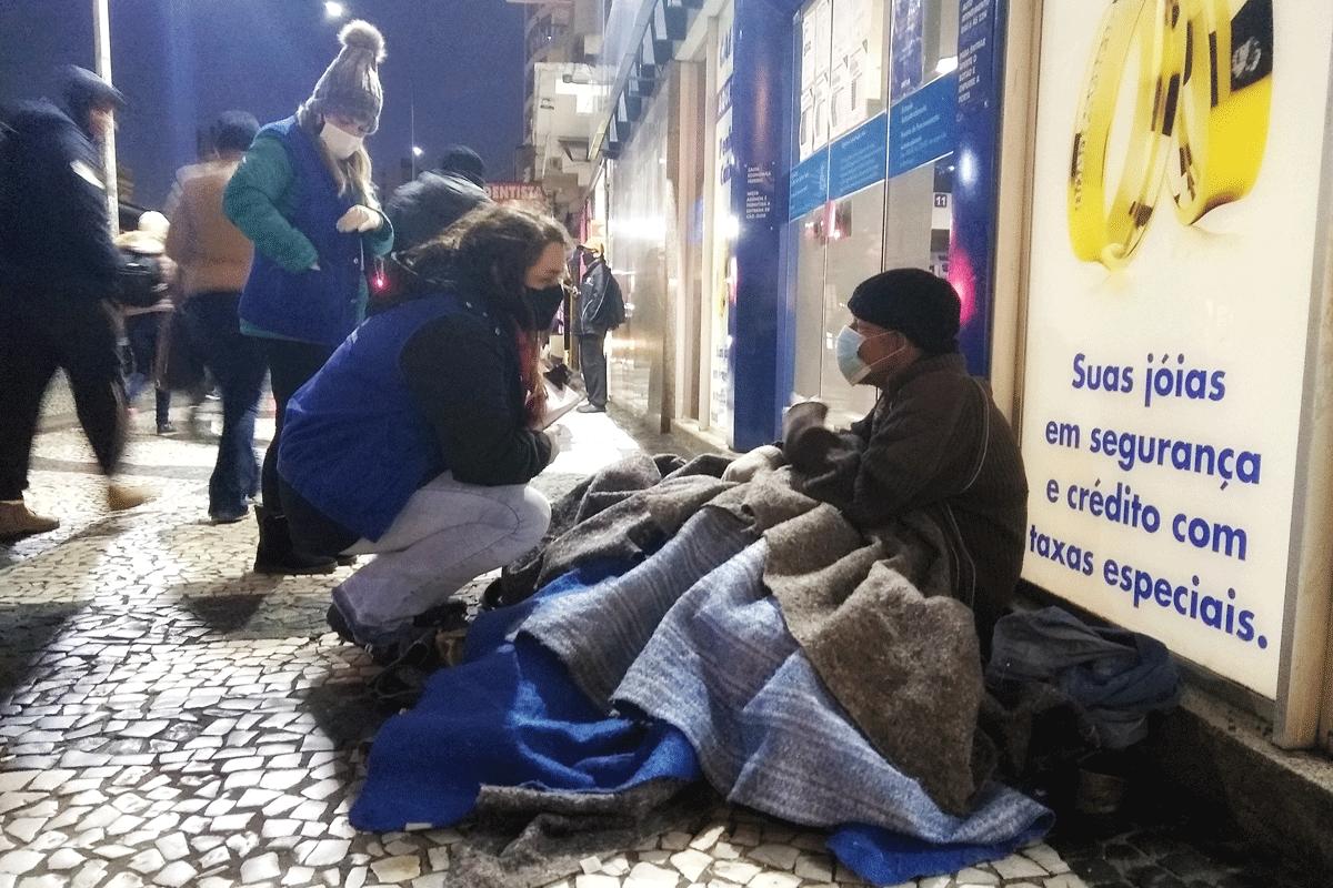 De colete azul, funcionária da prefeitura aborda pessoa em situação de rua em Curitiba –